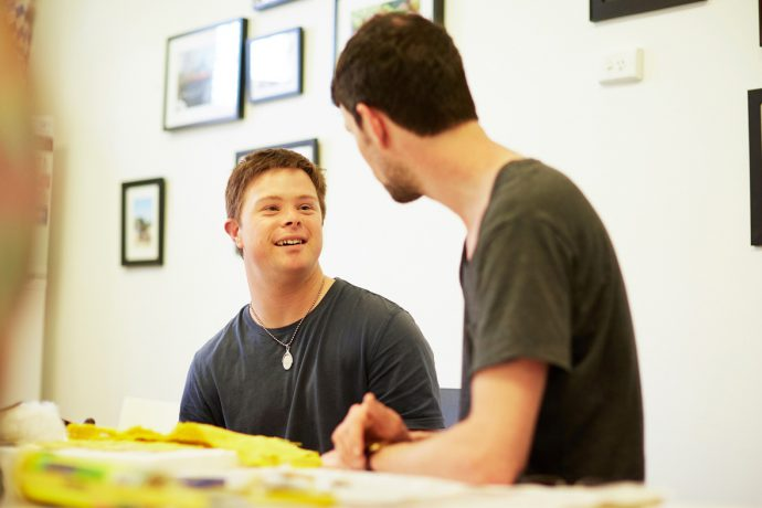 A young smiling man faces towards the camera and talks to another young man with an artwork between them on the table and artworks on the wall behind them.