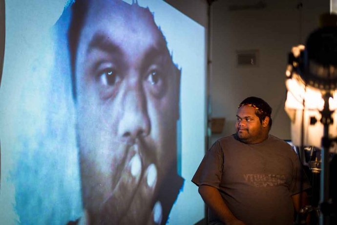 A young Aboriginal man sits on a chair and looks to his left, at a large digital portrait of himself projected onto a screen.