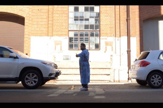 DADAA   man in street between two cars