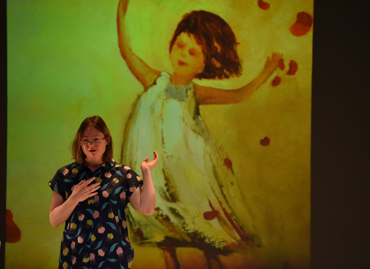 DADAA | Julia Hales on stage in front of image of dancing girl