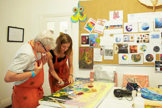 DADAA | careers and placements | artsworker and artist looking at a brightly coloured painting in an art studio