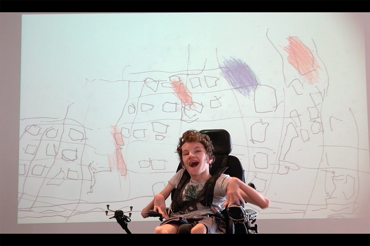 DADAA | young man in wheelchair performing in front of digital image