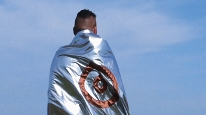 Man from the back wrapped in wilver sheet with red target on back
