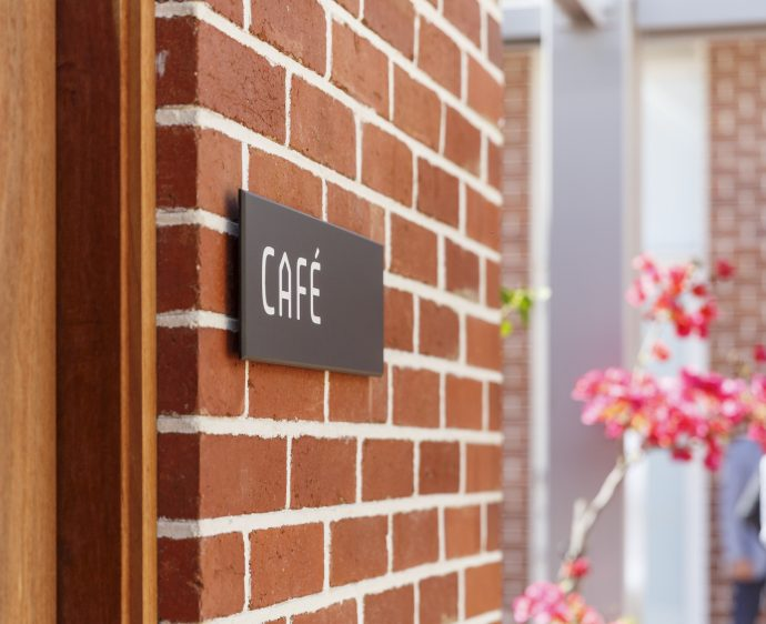 DADAA | Humble Pantry Fremantle | exterior | cafe sign | red brick wall | bougainvillea in background