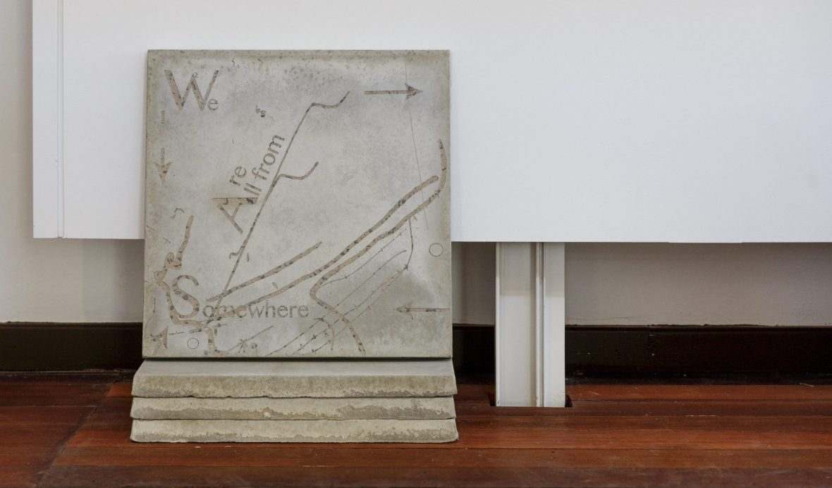 Stack of concrete slabs which have been laser cut with abstract map and text