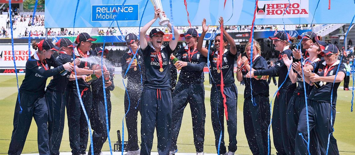 England Women's Cricket Team celebrating their World Cup win at the cricket ground. One player is holding up the trophy, while the others are spraying champagne. Red and Blue streamers are being thrown.