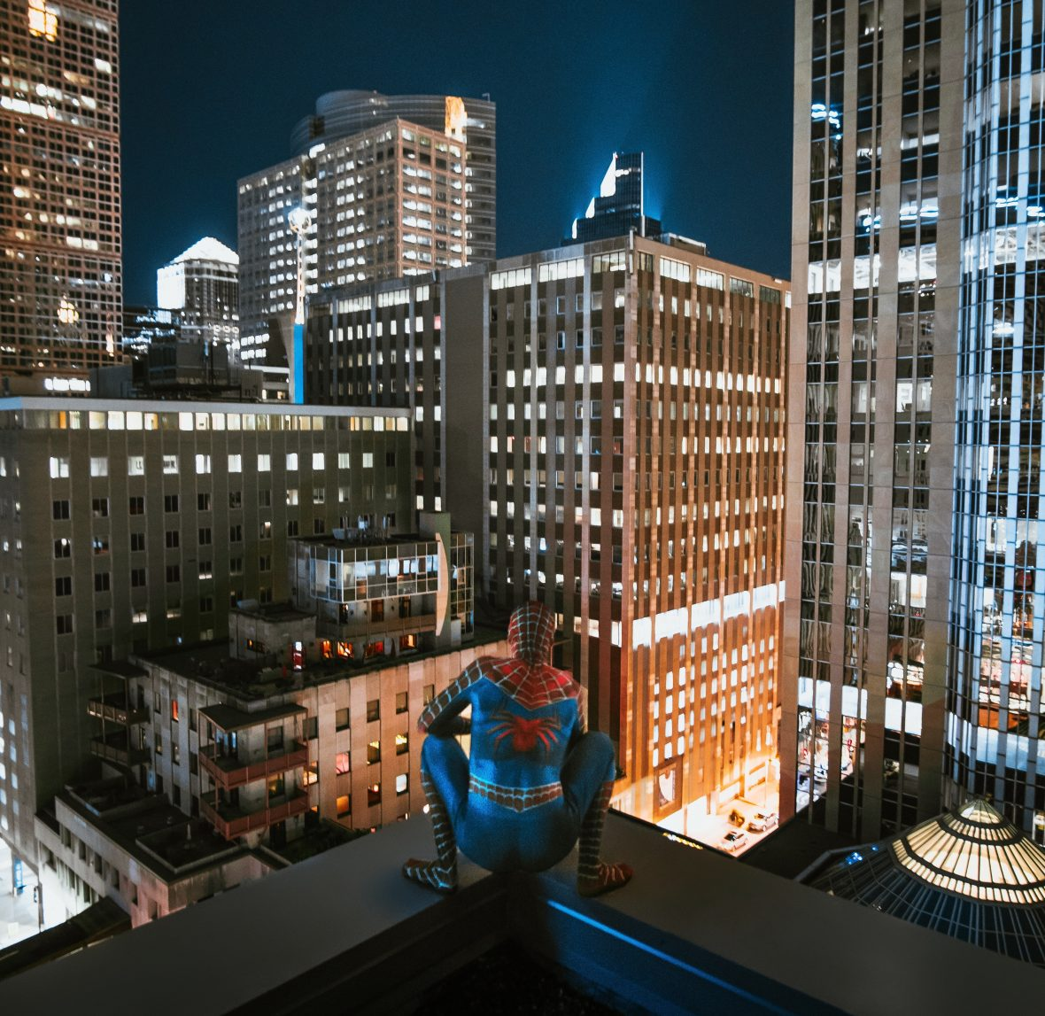 Spider-Man sitting on top of skyscraper, looking out at city at night