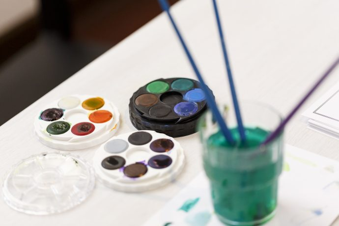 Photograph of watercolour paint palettes and brushes in a glass on a table