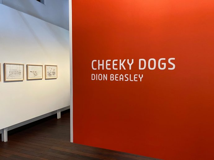 Interior of DADAA Fremantle Gallery Cheeky Dogs Exhibition, orange wall with the words Cheeky Dogs and Dion Beasley in white