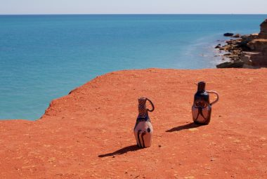 2 ceramic wonky pots sit at the edge of a red dirt cliff overlooking the ocean. they look lost and purposeful. their shadows, the only darkness in the vivid landscape.