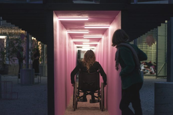 A long narrow corridor, bathed in pink fluro light, showing a person in a wheelchair navigating into the distance.