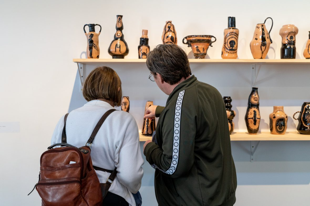 Two people standing and in front of two rows of ceramic sculptures