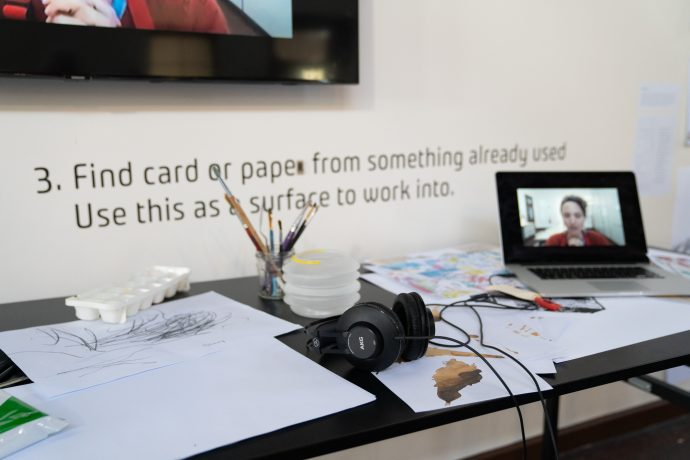Image from Homepage Exhibition of a table with drawing materials and an iPad