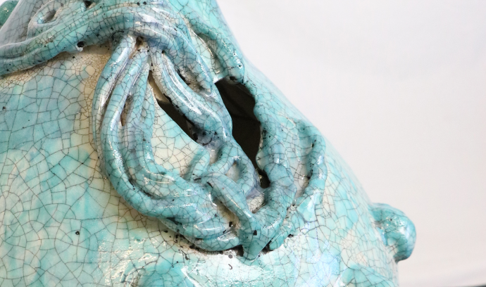 Photograph of ceramic vessel with pale turquoise glaze and craquelure