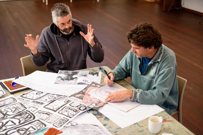 One-on-one mentoring at DADAA Fremantle. Male arts worker with beard sitting at table with artist who is developing storyboards for a graphic novel.